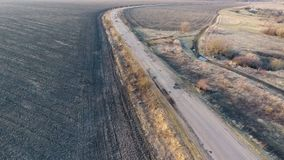 Driving fast on a highway. An aerial shot of orange vans driving fast on a highway stock video footage
