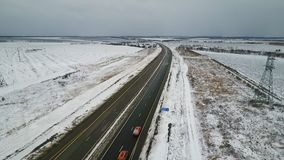 Driving fast on a highway during winter. An aerial shot of a highway during winter cars running fast on a highway stock video footage