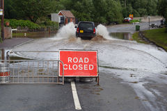 Driving through flood. A 4x4 vehicle drives through a flood, ignoring the Road Closed sign royalty free stock photos