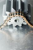 Driving-force of mechanical parts. Large cog-wheels being powerd by giant chain against scratched aluminum Stock Photo