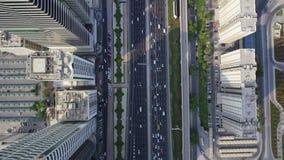 Cars driving in futuristic architecture of modern Dubai skyscraper panorama in amazing top drone aerial flight over. Driving in futuristic architecture of modern stock footage