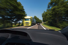 Driving during good weather conditions. View from passenger's seat, passing the truck, natural motion blur stock images