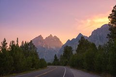 Driving through Grand Teton National Park at sunset. A road through the Tetons with a colorful sunset in the distance Royalty Free Stock Image