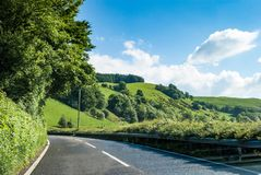Driving through the green hills and pastures of rural England. Typically English  paved country road, England, UK Stock Photos