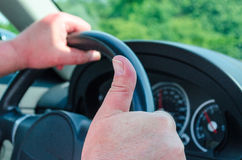Driving. Hand on the wheel, the other hand shows a thumbs-up Stock Photos