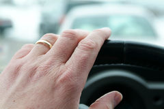 Driving Hands. Driver stuck in traffic. Hand is in sharp focus traffic is out of focus Royalty Free Stock Images