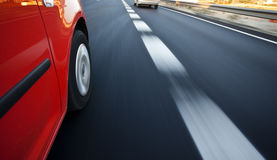 Driving at high speed. Red car driving at high speed in the highway Stock Image