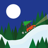 Driving Home for Christmas. A small red car with a christmas tree on the roof drives home through a winter landscape of snow and trees beneath a full moon Stock Photos