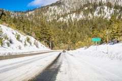 Driving on an ice and snow covered road through the Sierra mountains on a sunny day; Carson City road sign on the right; Nevada stock images