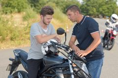 Driving instructor advising young man driving motorbike. Driving instructor advising young men driving a motorbike stock images
