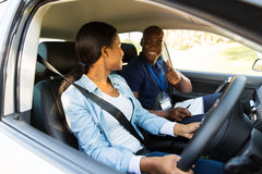 Driving instructor learner. Smiling driving instructor giving thumbs up to learner driver during test Royalty Free Stock Images