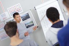 Driving instructor pointing at board in classroom. Driving instructor pointing at board in a classroom Stock Images