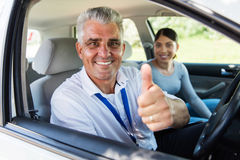 Driving instructor thumb up. Handsome senior driving instructor giving thumb up Stock Photo