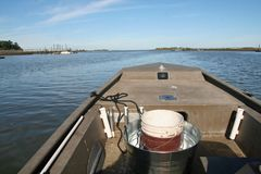 Driving jon boat on saltwater to go pick oysters in Charleston South Carolina stock photo