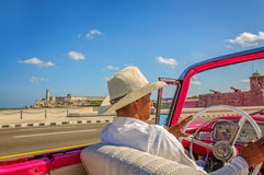 Driving on Malecon in Old Havana. Havana, Cuba -March 14, 2016: Taxi driver in a white traditional hat driving a vintage American car on Malecon - the main Stock Photo