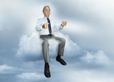 Driving man. A business man in a shirt and tie drives an invisible vehicle in the clouds. Concept for alternative modes of transportation. Concept for comfort Stock Images