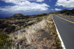 Driving Maui Island's Coastline Roads. On Maui Island, Hawaii, this is a coastline road going by a cinder cone originating from its last volcanic eruption in Royalty Free Stock Photos