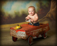 Driving me crazy. Baby driving antique car toy Royalty Free Stock Photos