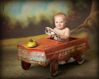 Driving me crazy. Little boy driving antique toy car Stock Photo