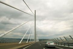 Driving the Millau Viaduct. Silver car driving on the beautiful Millau viaduct, Aveyron, France, on a clouded day. The cables of the bridge are clearly visible Stock Images
