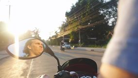 Close up of man driving motorbike on tropical island during beautiful sunset in slow motion while traveling. Thailand stock video footage