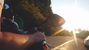 Close up of men hand driving motorbike to the sun on tropical island while traveling during beautiful sunset in slow stock video footage