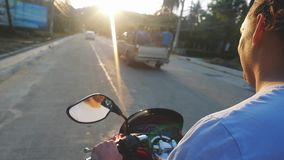 Handsome man driving motorbike on tropical island during beautiful sunset in slow motion while traveling. Vacation stock footage