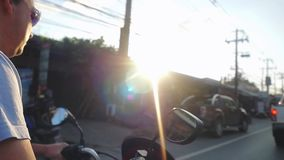 Motorcyclist wearing sunglasses drives motorcycle while traveling on tropical island during beautiful sunset in slow stock video footage