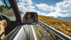 Driving At Mountain Road. Driver In A Car Side Mirror. Road Trip Journey Lifestyle Concept Royalty Free Stock Photography