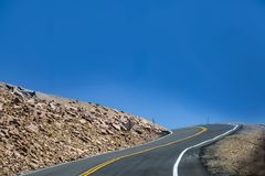 Driving mountain road into a hairpin curve with drop-off to one side and just the sky showing up above the tree line on Pikes Peak. Colorado stock image