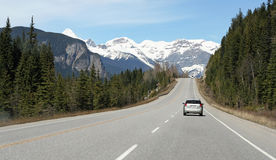 Driving in mountains. Car drives along road in Rocky Mountains, Canada Stock Photography