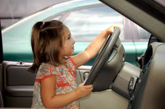 Driving in my car. Four year old girl driving a car Stock Image