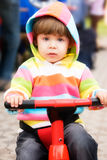 Driving My First Bike. Little girl in colorful hood jacket driving red scooter royalty free stock photography
