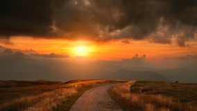 Driving on narrow mountain road at sunset Royalty Free Stock Image