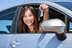 Driving new rental car or drivers license concept. Young teenager woman driver holding car key driving her new car. Beautiful multiracial Asian woman smiling stock photography