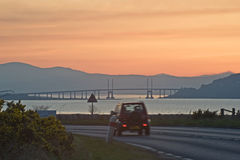 Driving north along the A96. Driving north at sunset along the A96 to Inverness with the Kessock Bridge visible in the distance Royalty Free Stock Photography