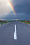 Driving om empty road under the rainbow