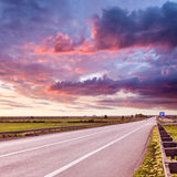 Driving on an open asphalt road at sunset Royalty Free Stock Photos
