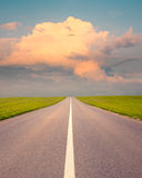 Driving on an open asphalt road at sunset Stock Image