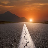 Driving on open road towards the mountain at sunset Royalty Free Stock Photography