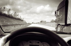 Driving overtake lorry. Monochrome image of overtaking lorry, driving down highway or dual carriageway stock photography