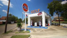 Driving past old gulf gas station in Waco Texas stock video