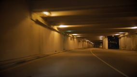 Driving POV. The car travels along a long tunnel. Driving POV. The car travels at night through a long tunnel stock video footage