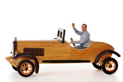 Driving Proud. Man proudly waving from the driver's seat of a life-sized model wooden car Royalty Free Stock Photos