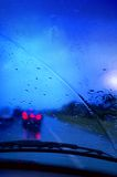 Driving in rain. A car windshield with wiper and rain droplets following a car that has stepped on their brakes Stock Photography