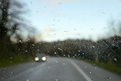 Driving in the rain. Driving a car in the rain, on a rainy day at sunset. Drive under the rain Royalty Free Stock Image