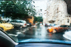Driving in the rain. Driving with rain drops on windscreen ,in the city Royalty Free Stock Photos