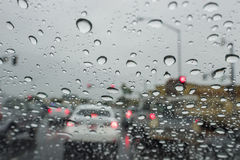 Driving in the rain with many water drops in the glass Royalty Free Stock Image