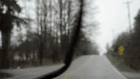 Driving in rain, out of focus background and headlights, dreary day, handheld. Driving during rain, passenger viewpoint, out of focus background and headlights stock footage