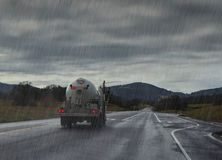 Driving in rain. Rainy road with liquid truck. Stock Photo